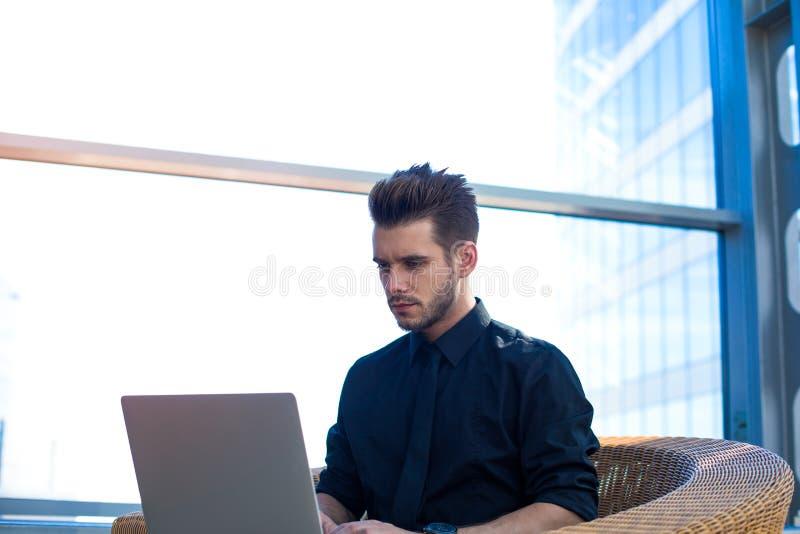 Dirección masculina acertada que busca la información sobre sitio web vía el cuaderno imagenes de archivo