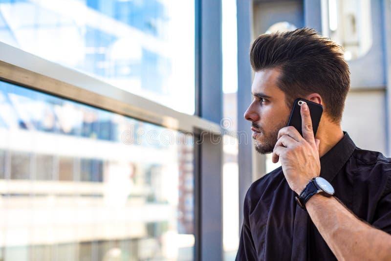Dirección masculina barbuda que llama vía el teléfono móvil durante trabajo en oficina imagenes de archivo