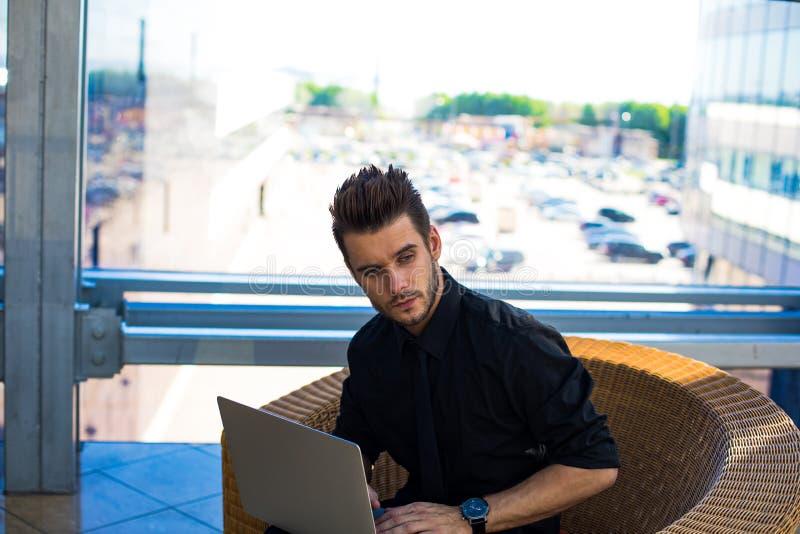 Dirección masculina pensativa usando netbook mientras que espera conferencia en empresa imagen de archivo libre de regalías