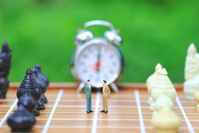 Dirección para el juego del éxito, situación miniatura del hombre de negocios en fondo del tablero de ajedrez y del ajedrez, la i foto de archivo libre de regalías