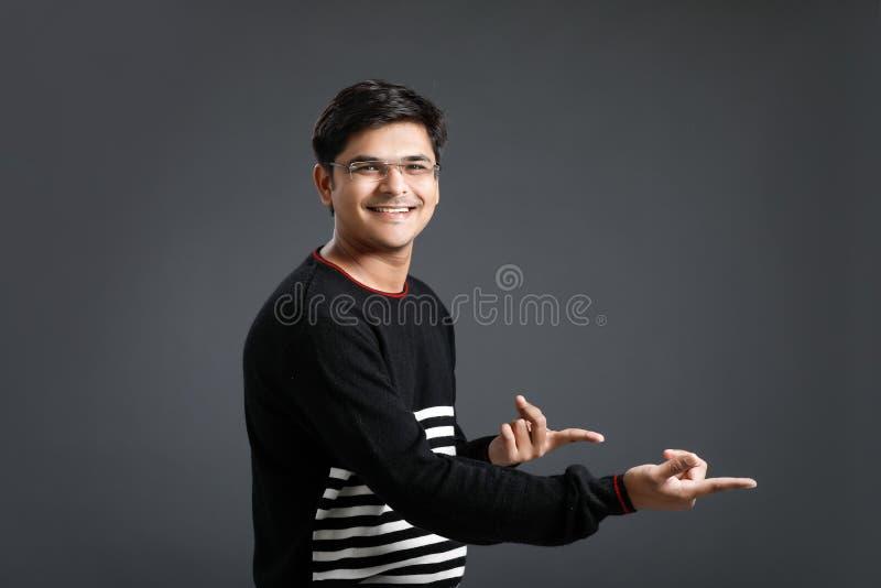 Direcci?n india de la demostraci?n del hombre joven con la mano imagenes de archivo