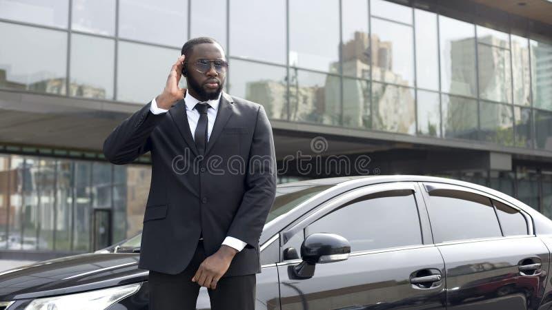 Direcciones en auriculares, seguridad del jefe del trabajador afroamericano de la seguridad que escuchan fotografía de archivo