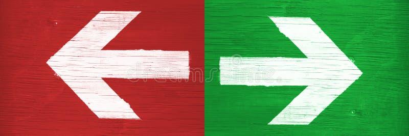 Direcciones punteagudas de las flechas blancas a la derecha y a la izquierda pintado manualmente en fondo de madera verde y rojo  foto de archivo libre de regalías