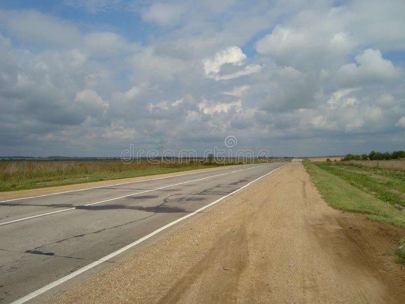 Direct asphalt road through the countryside under the sky, on which the clouds float stock photography