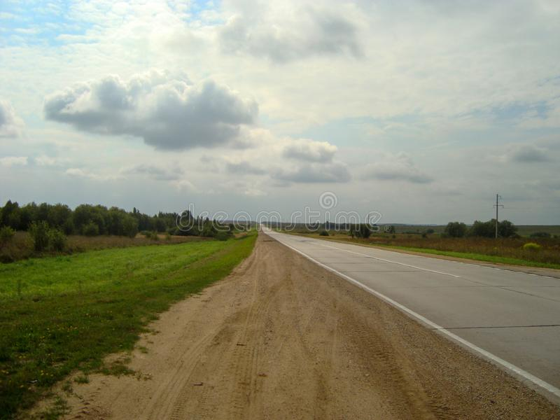 Direct asphalt road through the countryside under the sky, on which the clouds float royalty free stock photos