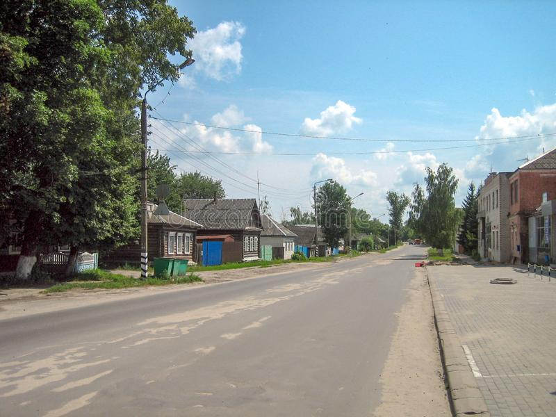 Direct asphalt street along the village with one-and two-storey houses royalty free stock photography
