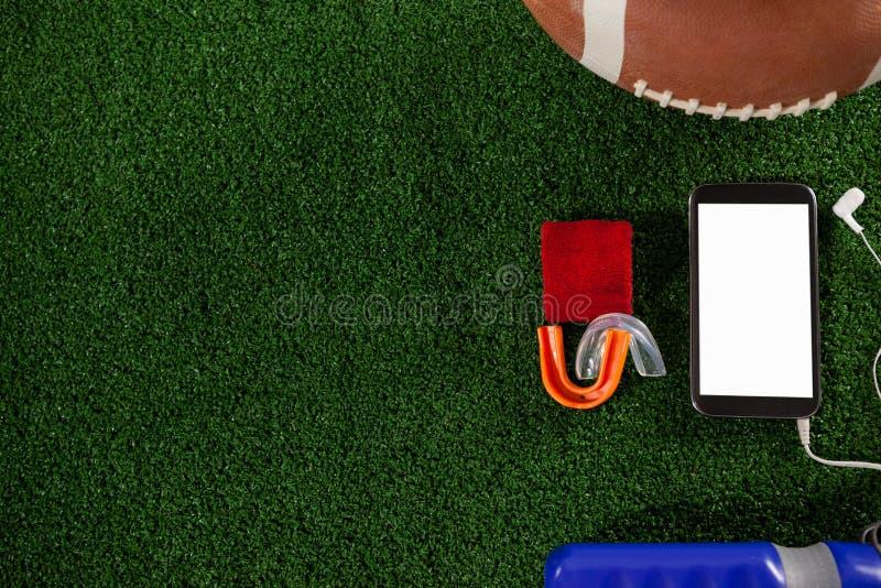 Direct boven schot van slimme telefoon door Amerikaanse voetbal stock afbeeldingen