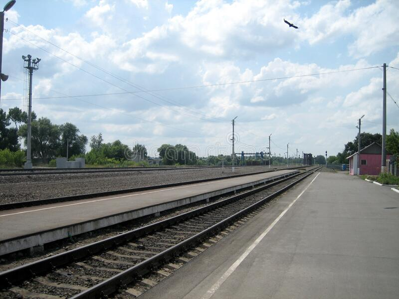 Direct railway track through a small station outside the city on a summer day. Steel rails are laid along a low platform. A bird of prey hovers in the sky stock photo