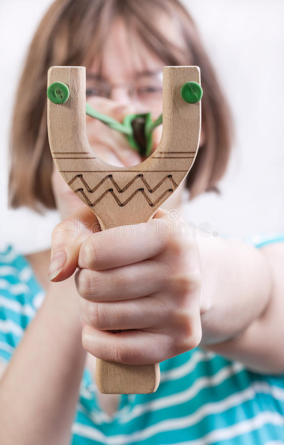 Direct view of girl pulling band of slingshot stock images