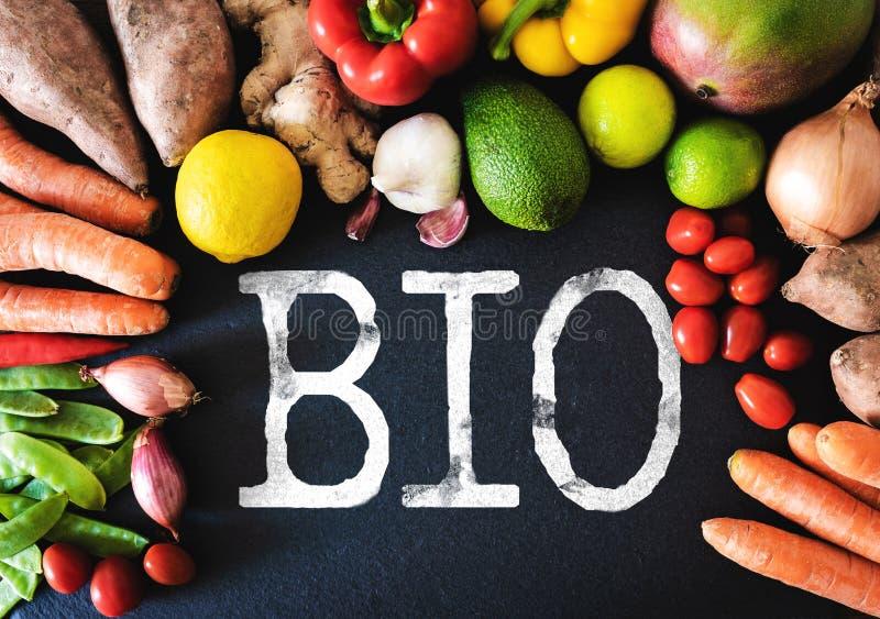 Directamente sobre el primer de verduras y de frutas orgánicas frescas encendido en fondo de la pizarra con la palabra BIO fotografía de archivo