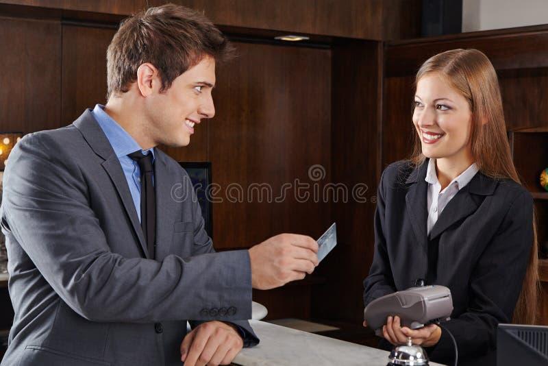 Directeur à la réception d'hôtel payant avec la carte de crédit images libres de droits