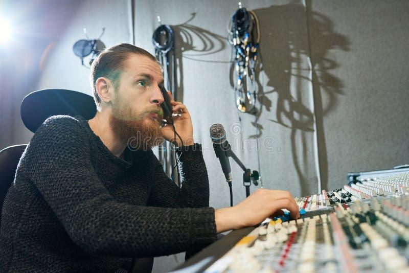 Directeur avec des écouteurs dans le studio d'enregistrement photo stock