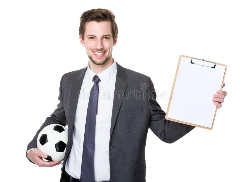 Directeur caucasien de scooer se tenant avec le football et montrant avec image libre de droits