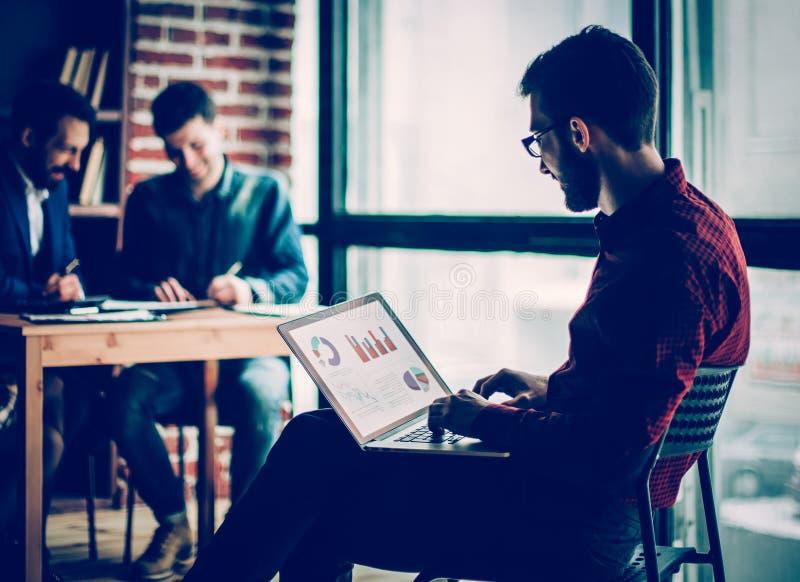Directeur commercial travaillant avec les graphiques financiers sur l'ordinateur portable image libre de droits