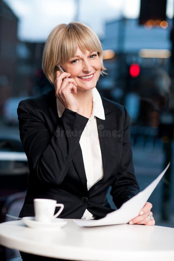 Directeur communiquant par l'intermédiaire du téléphone portable en café photo stock