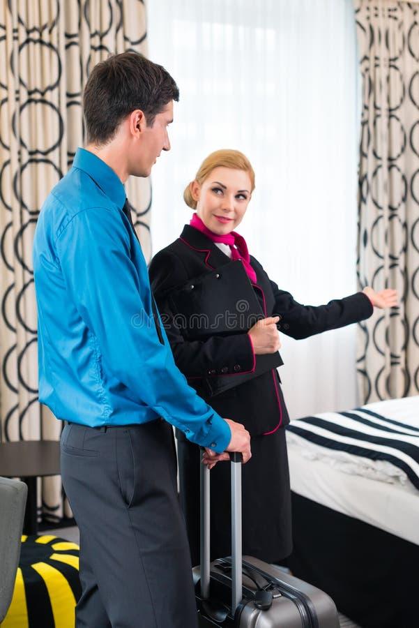 Directeur d'hôtel souhaitant la bienvenue à l'invité montrant la pièce photo libre de droits