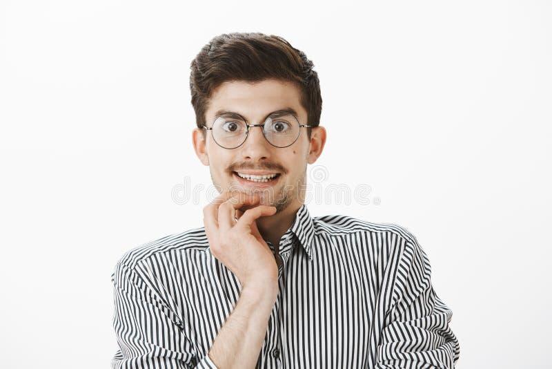 Directeur de bureau ringard intéressé regardant avec la tentation par des verres le nouvel ordinateur dans le magasin, souriant n photographie stock libre de droits