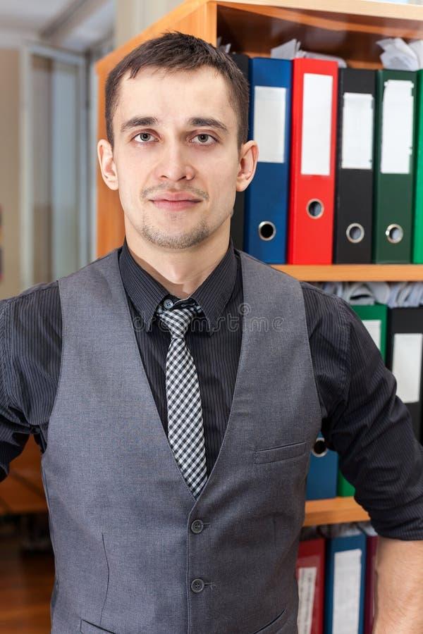 Directeur de comptabilité caucasien se tenant devant le coffret avec des dossiers de documentation photographie stock libre de droits