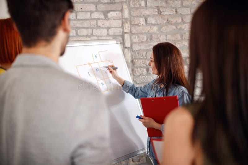 Directeur de femme d'affaires présent sur le tableau blanc à son collègue photos libres de droits