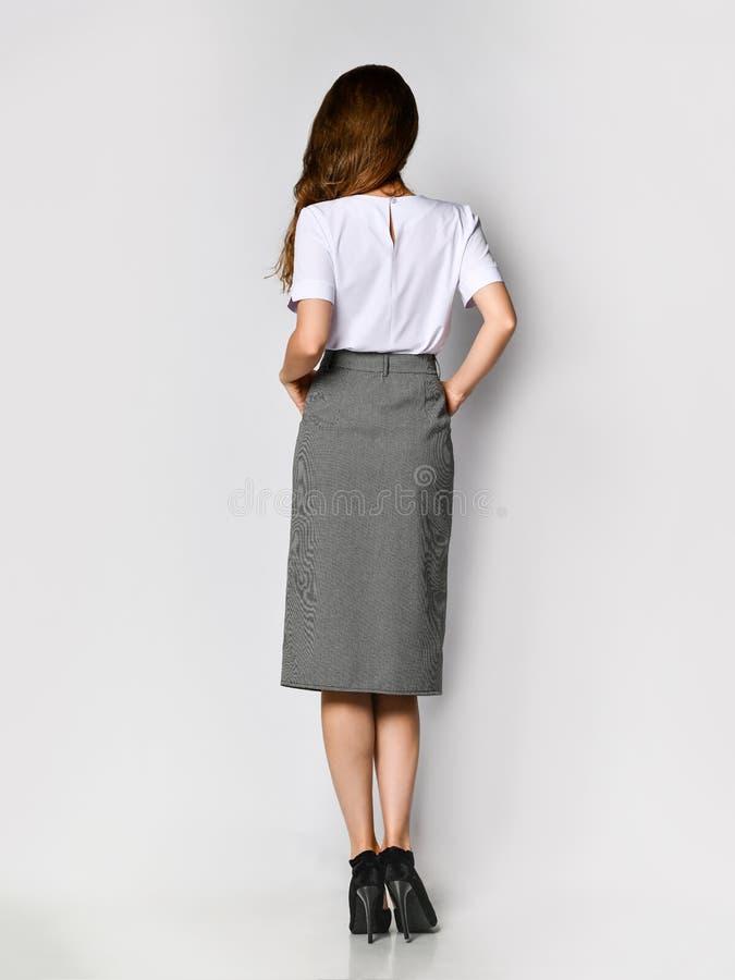 Directeur de femme dans un nouveau chemisier blanc et une jupe grise de bouton-, se tenant posants de nouveau ? la cam?ra, int?gr images stock