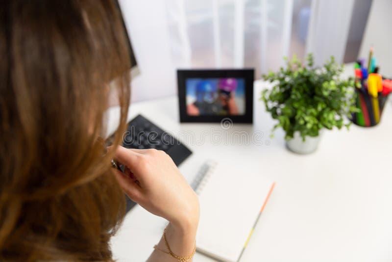 Directeur de jeune femme s'asseyant et pensant dans l'espace de travail avec l'ordinateur et le carnet photos stock