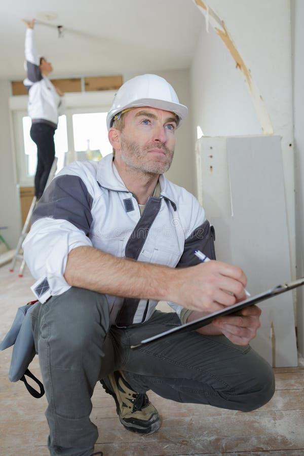 Directeur de rénovation écrivant sur le presse-papiers image stock