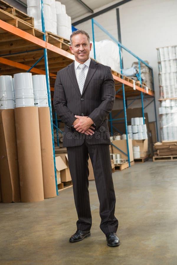 Directeur de sourire d'entrepôt se tenant avec des mains ensemble photos stock