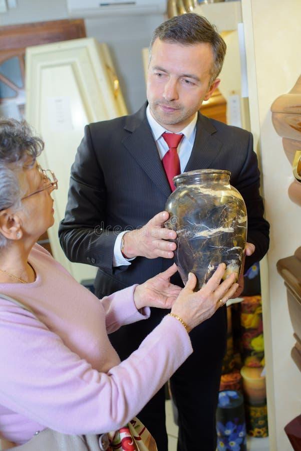 Directeur des pompes funèbres avec la veuve choisissant l'urne photographie stock libre de droits