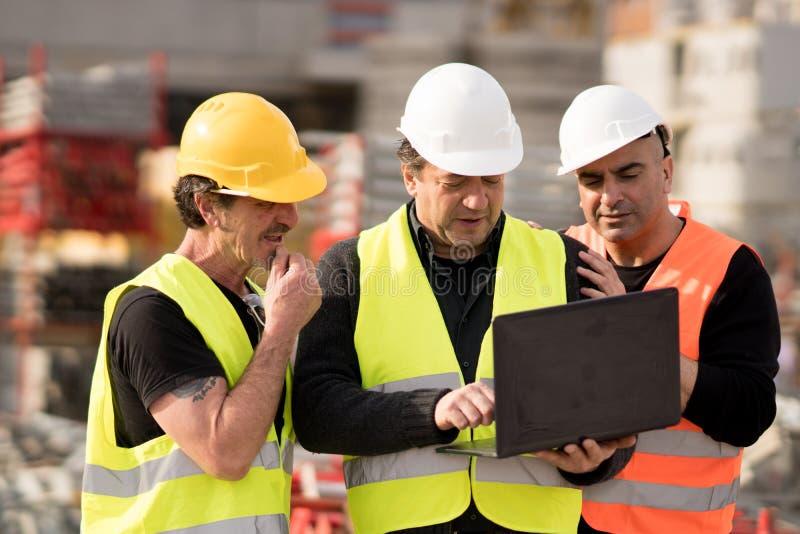 Directeur des travaux de construction et deux travailleurs à l'aide de l'ordinateur portable de PC photos stock