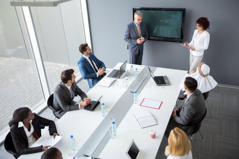 Directeur en vrouwelijke hulpgreep commerciële vergadering in bedrijf royalty-vrije stock afbeelding
