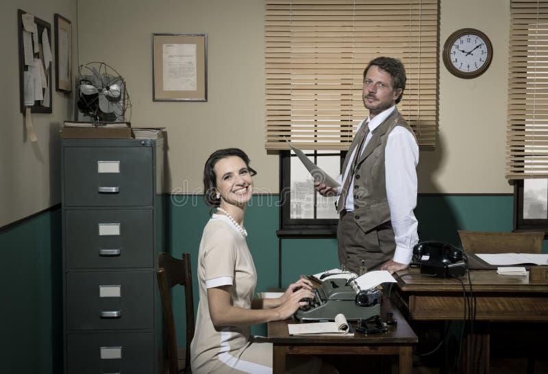 Directeur et secrétaire travaillant ensemble dans le bureau images libres de droits