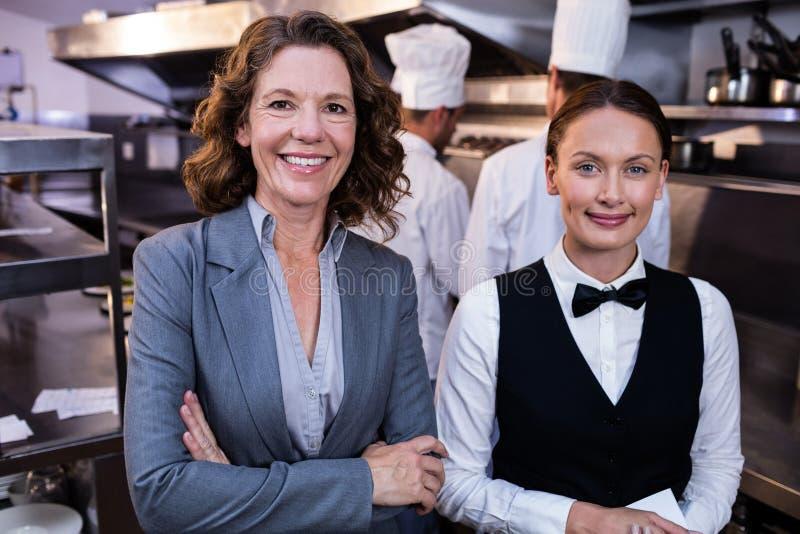Directeur et serveuse de restaurant souriant dans la cuisine commerciale photographie stock