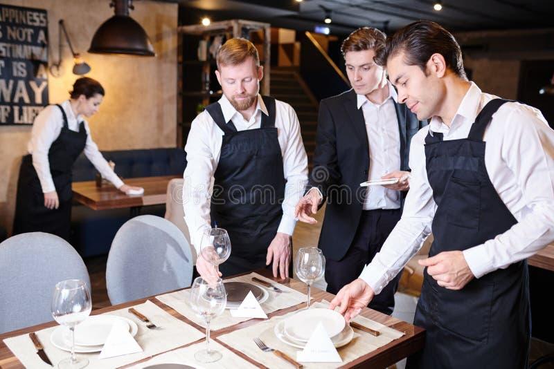 Directeur expliquant l'arrangement de table aux serveurs photographie stock
