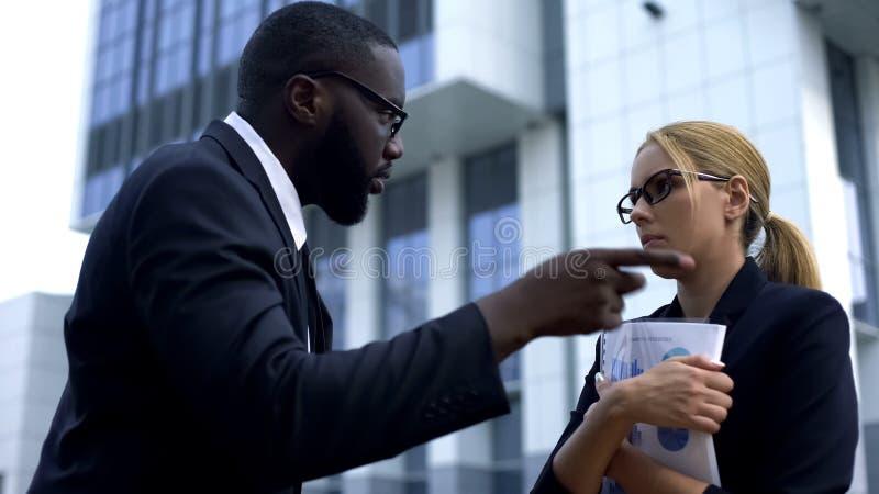 Directeur fâché mettant le feu à l'employé féminin pour le travail manqué de date-butoir, renvoi photo libre de droits
