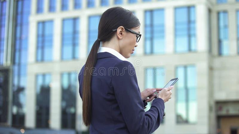 Directeur féminin employant l'application de smartphone envoyant l'email, calendrier en ligne photo stock