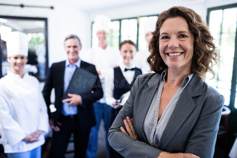 Directeur féminin heureux se tenant avec des bras croisés photographie stock