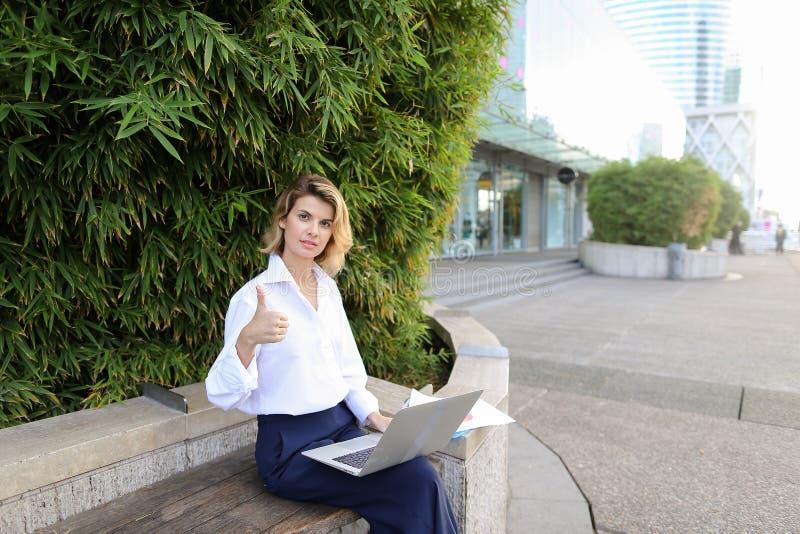 Directeur féminin réussi travaillant avec l'ordinateur portable et les papiers en air ouvert, montrant des pouces  photos libres de droits