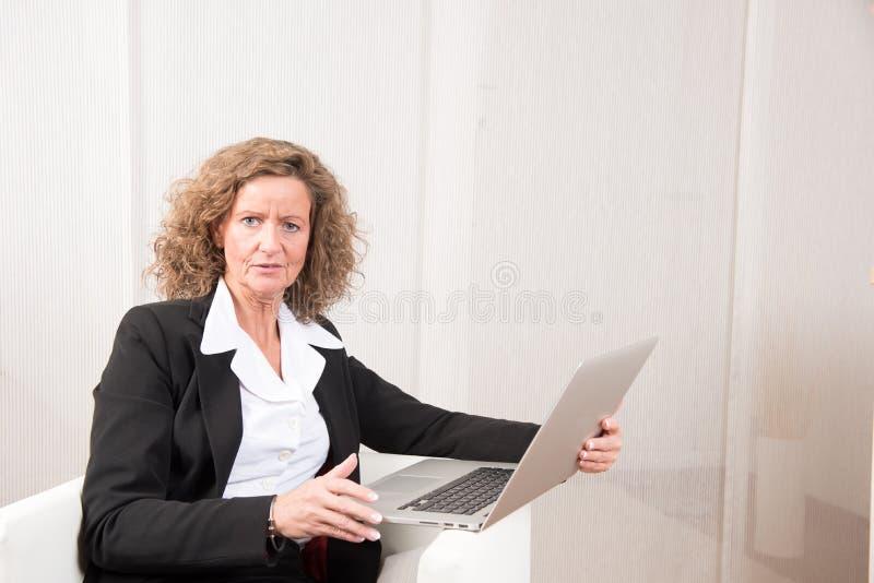 Directeur féminin travaillant avec l'ordinateur portable photos libres de droits