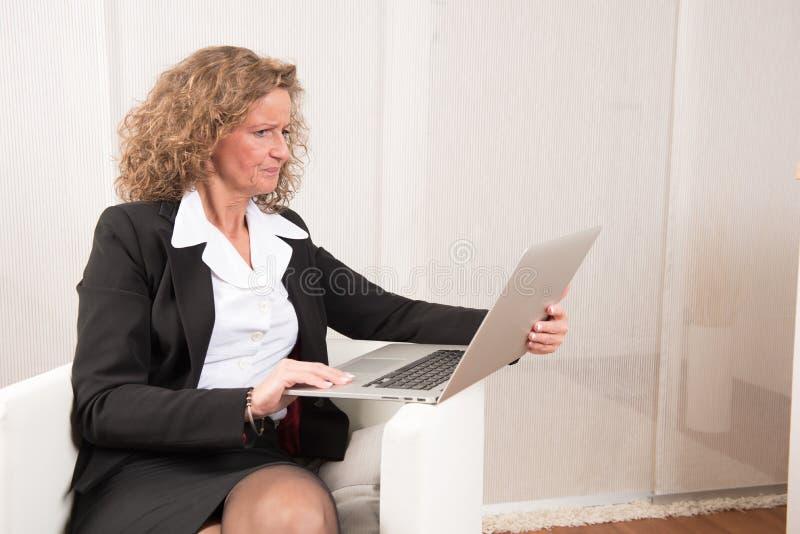 Directeur féminin travaillant avec l'ordinateur portable photographie stock