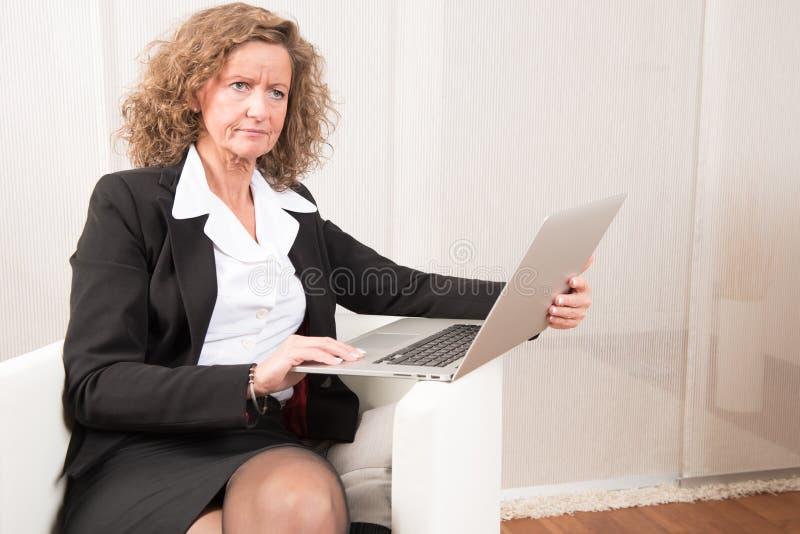 Directeur féminin travaillant avec l'ordinateur portable images libres de droits