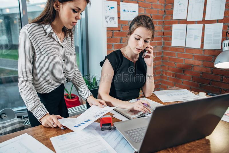 Directeur général féminin occupé parlant au téléphone tandis que son assistant lui montrant des statistiques financières photo libre de droits