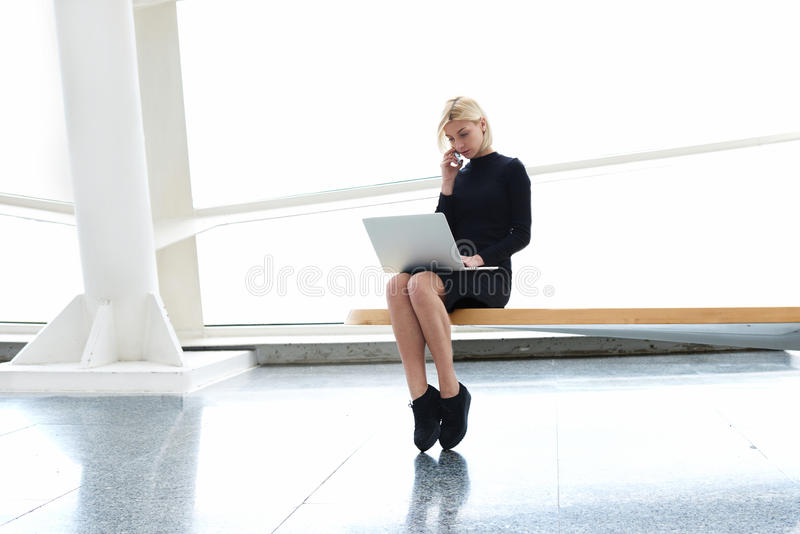Directeur général qualifié de femme sûre ayant la conversation de téléphone portable avec son secrétaire photographie stock