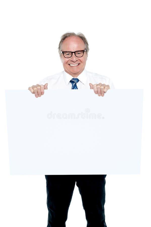 Directeur marketing supérieur retardant un panneau blanc d'annonce image libre de droits