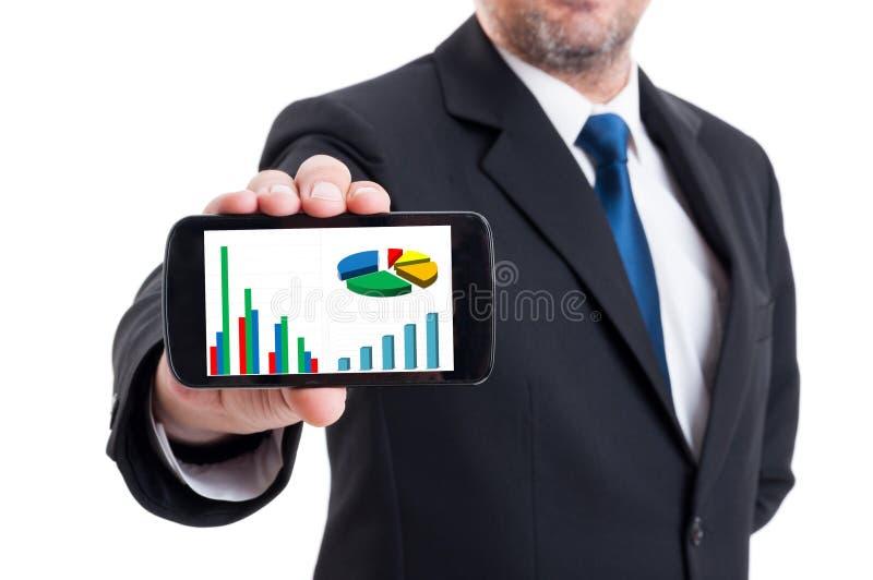 Directeur marketing tenant le smartphone avec élever le char financier photo stock
