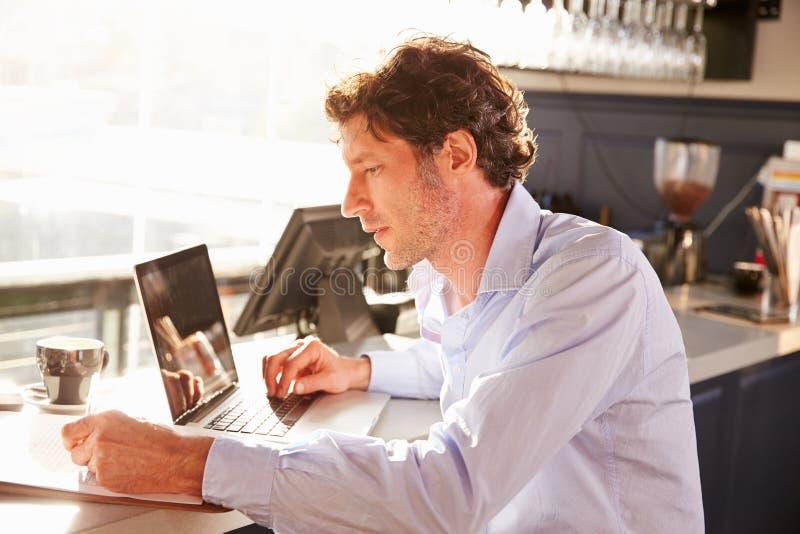 Directeur masculin de restaurant travaillant sur l'ordinateur portable photo libre de droits