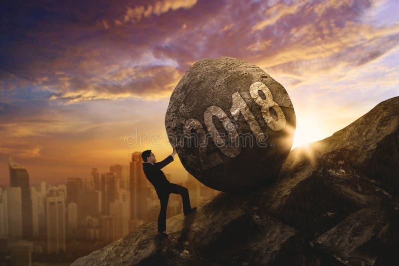 Directeur masculin poussant une pierre avec les numéros 2018 image libre de droits