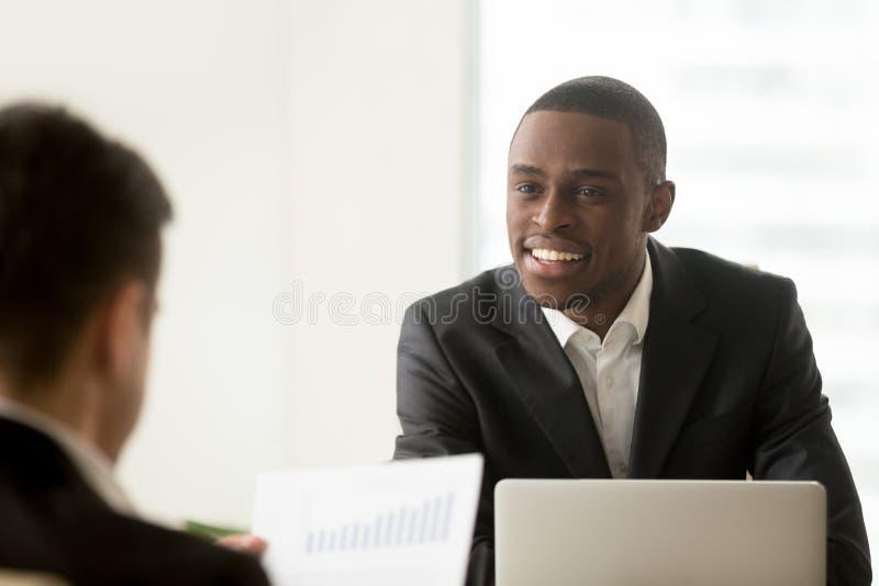 Directeur noir communiquant avec le client blanc image stock
