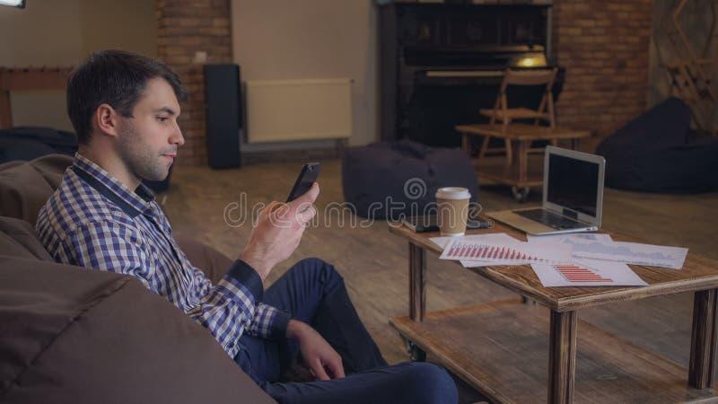 Directeur parlant au téléphone tout en se reposant dans un fauteuil, un ordinateur portable est sur la table image libre de droits