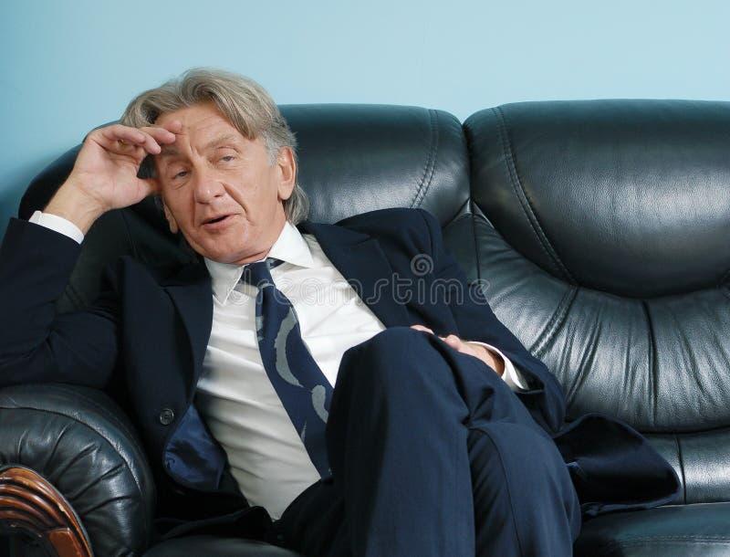 Directeur pensant sur le sofa en cuir photo libre de droits