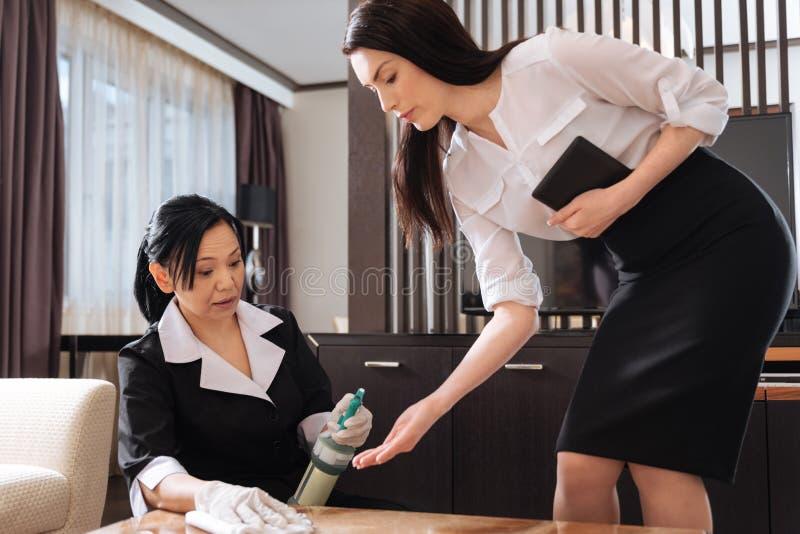Directeur professionnel de ménage vérifiant le travail du personnel photo stock